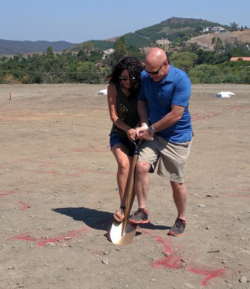 Husband and wife, holding golden shovel to signify breaking ground on new custom home lot in Temecula
